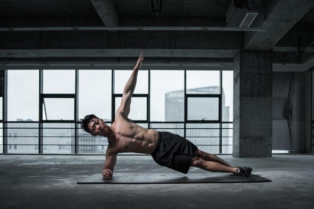 Muž ktorý cvičí v budove s presklenou stenou