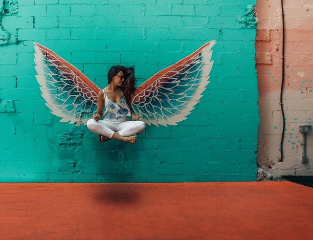 Anjelské krídla namaľované na tehlovej stene, pred ktorými sedí žena v tureckom sede