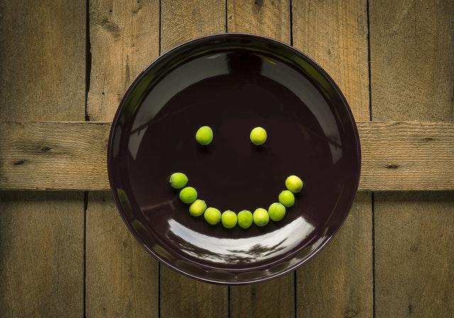 Hnedý tanier so zeleným hráškom v tvare smajlíka.jpg
