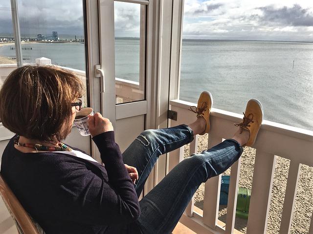 Žena na balkóne pije kávu a má vyložené nohy na bielom zábradlí.jpg